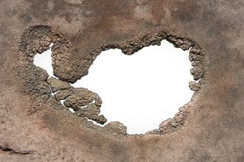 44309329 - a hole with jagged decaying edges isolated on white